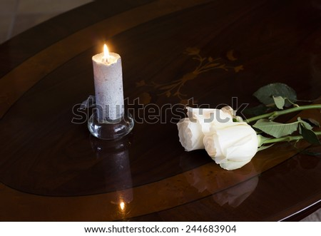 White roses on a wooden dark table with a candle.