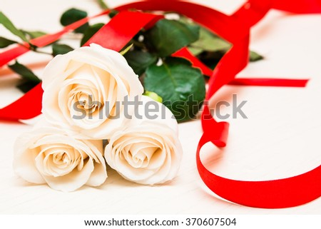 White roses with red ribbon on a light wooden background. Women' s day, Valentines Day, Mothers day. Copy space, selective focus - stock photo