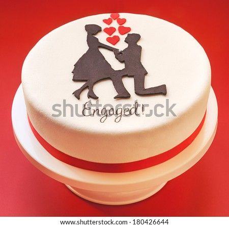 White round cake on red background, decorated with male and female silhouette of sugar on top.  - stock photo