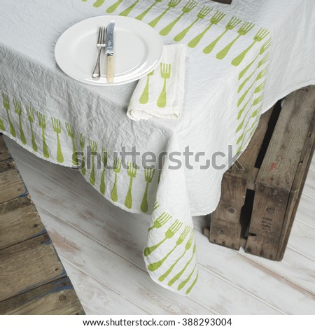 White round dinner plate containing dining fork and knife, beside folded table napkin with green fork pattern design, placed on corner of table covered with green fork pattern design.