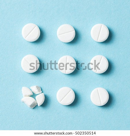 White round pills with one broke into small pieces on blue background