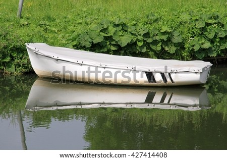 white rowboat with cover on the banks secured with reflection in water - stock photo