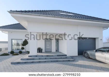 White royal residence with garage and new silver car - stock photo