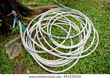 White rubber water hose or tube for garden with grass background.