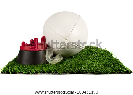 White rugby ball on tee placed on a patch of grass with gum gaurd - stock photo