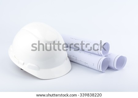 White safety helmet and Scrolls of engineering drawings. - stock photo