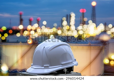 white safety helmet standing in front of oil refinery background - stock photo