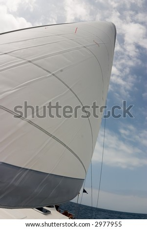 white sail against a background of cloudy sky