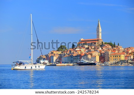 White sail boat approaches the harbor of old town near the Adriatic sea, Rovinj, Croatia - stock photo