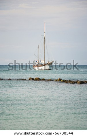 White sailboat anchored in the Caribbean with rocks in the foreground.