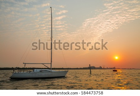 White sailboat and golden sky before sunset - stock photo