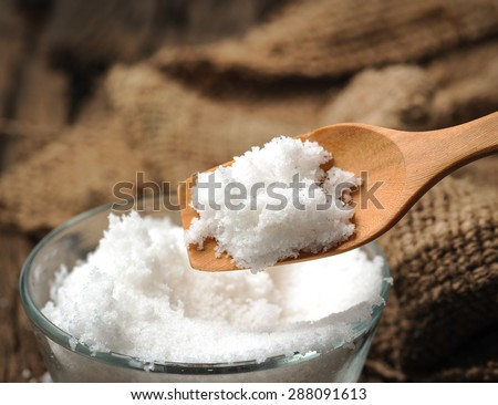 white salt in wooden spoon on wood