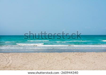 white sand beach with blue sea background. - stock photo