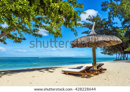 White sand beach with lounge chairs and umbrella in Mauritius Island, Indian Ocean - stock photo
