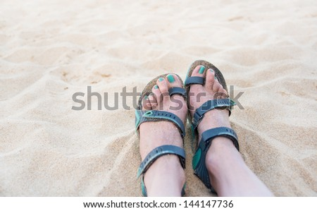 White Sand on Beach with Female Feet Wearing Minimal Sport Sandals in Gray Green Color
