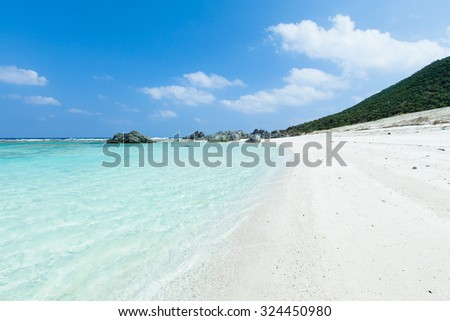 White sand tropical beach with clear water of a coral lagoon, Iheya Island, Okinawa, Japan - stock photo