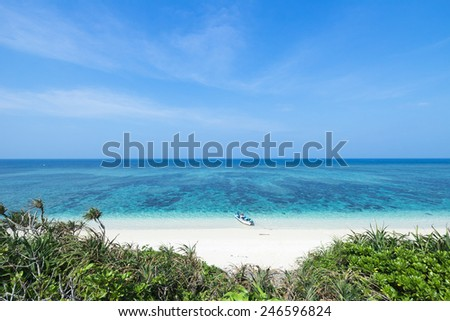 White sand tropical paradise beach and clear blue water of a deserted coral island, Okinawa, Japan - stock photo