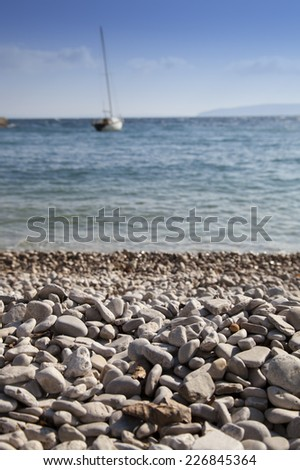 White sandy beach with rough high sea, sail boat and sunny blue sky in the background, selective focus on stones, romantic blue toned, high resolution photo - stock photo