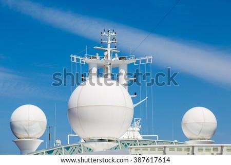 White Satellite and Communication Equipment Against Sky on Cruise Ship - stock photo