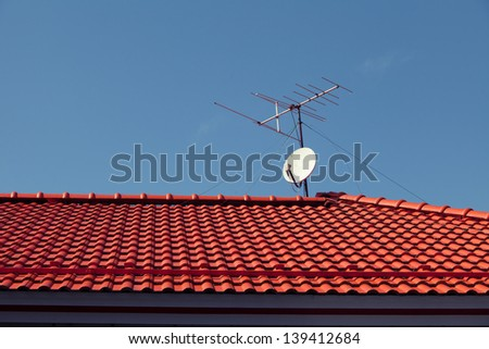 White Satellite dish with sky on red roof  - stock photo