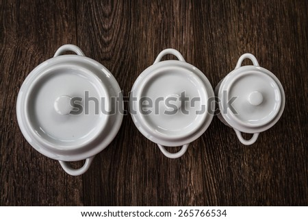 White saucepans with covers on brown wooden background, side view - stock photo