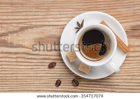 White saucer and cup of coffee espresso decorated cinnamon stick, star anise, cane sugar and coffee beans on textured rustic wooden table. Top view with place for text. Fresh hot coffee with foam. - stock photo