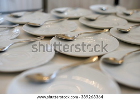 White saucer and spoon for tea and drinking coffee with dessert. Tableware utensils for coffee and tea for serving guests at banquet. Served table in the restaurant. Preparation of breakfast buffet. - stock photo