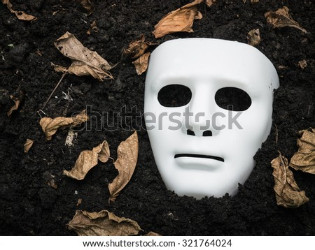White Scary Halloween mask on the ground - stock photo