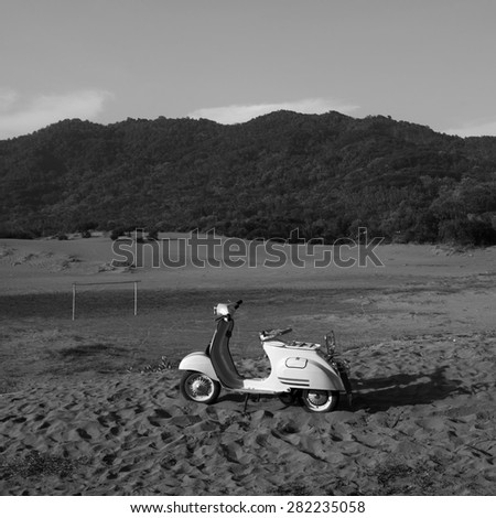 white scooter in the dune - stock photo