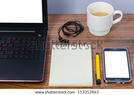 White screen laptop and mobile phone with blank notebook yellow pen in-ear headphone and a white cup of hot coffee on brown wooden table