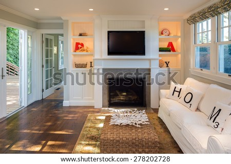 White seating arrangement, couch, sofa in mid century modern home with fire place, tv in open floor plan leading to outdoors. - stock photo