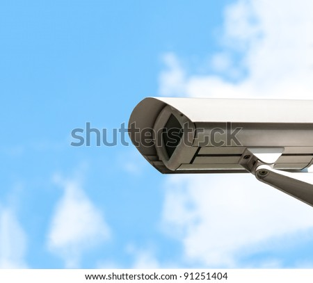 White security camera. Blue cloudy sky in background. A lot of copy space. - stock photo