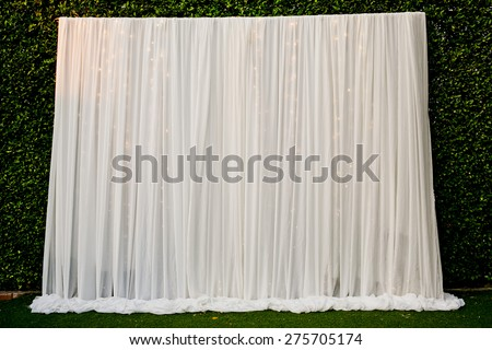White see through fabric curtain decorate with the lights in wedding ceremony. Wedding Backdrop. - stock photo
