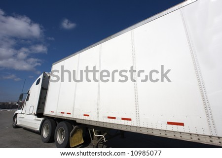 White Semi Truck parked under clouds. - stock photo