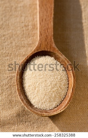 White semolina grains portion on wooden spoon closeup lying on table cloth, coarsely grains healthy raw food heap in day light, vertical orientation, nobody. - stock photo