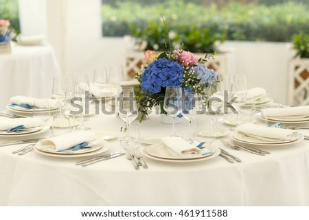 White serviettes and blue ribbons lie over the festive crockery