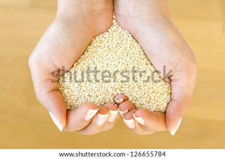 White sesame seeds in woman's hands forming heart shape - stock photo