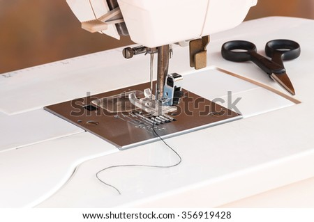 White sewing machine with scissors and thread