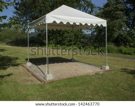 White shade structure set up on a lawn.