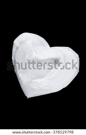 White shaving foam heart shape on black background - stock photo