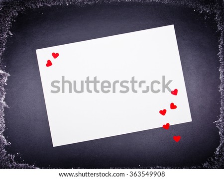 white sheet of paper on the black board decorated with red hearts