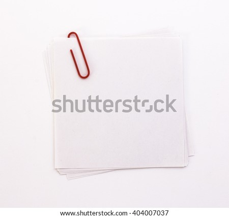 white sheet of paper with red paper clip on a white background