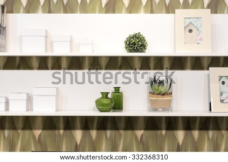 White Shelves with Various Stylish Items on Green Dated Wallpaper