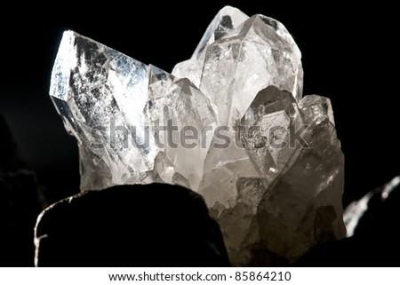 white shining rock mountain crystall quarz on black ground - stock photo