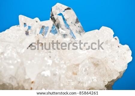 white shining rock mountain crystall quarz on blue ground - stock photo