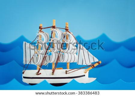 White Ship on blue wave with paper and sun. Travel and adventure concept.
