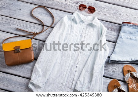 White shirt and flip flops. Light blue shorts and bag. Girl's flax shirt on display. New items at low price. - stock photo