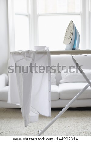 White shirt on ironing board in living room - stock photo