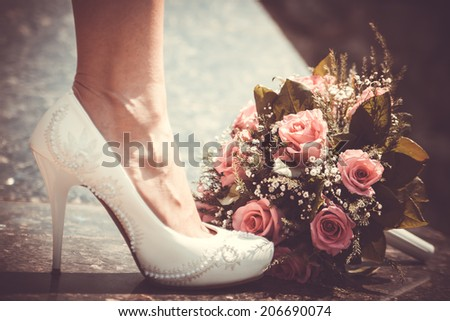 White shoe of the Bride next to wedding bouquet. Vintage wedding theme background - stock photo