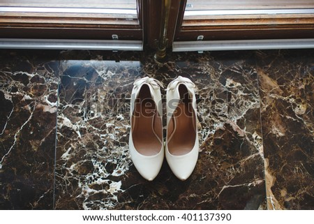 White shoe of the Bride on the marble floor. vintage wedding theme background - stock photo